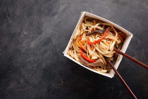 Nudeln in einer box mit gemüse und rindfleisch.