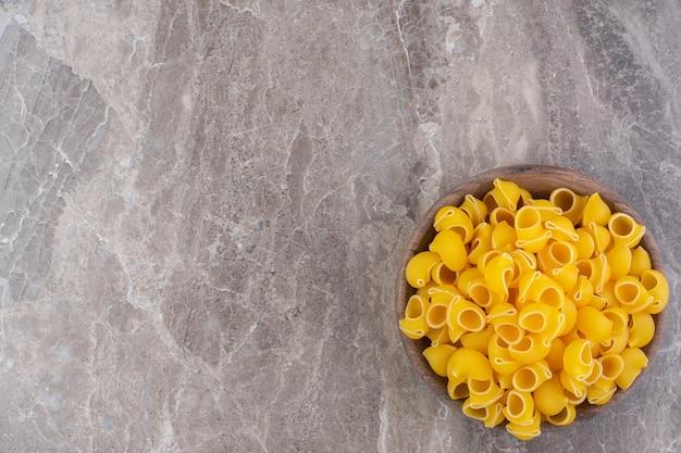 Nudeln in einer schüssel auf die marmoroberfläche geben