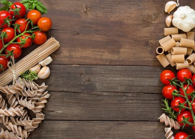 Nudeln, knoblauch, kräuter und tomaten auf brauner hölzerner tischoberansicht mit kopienraum