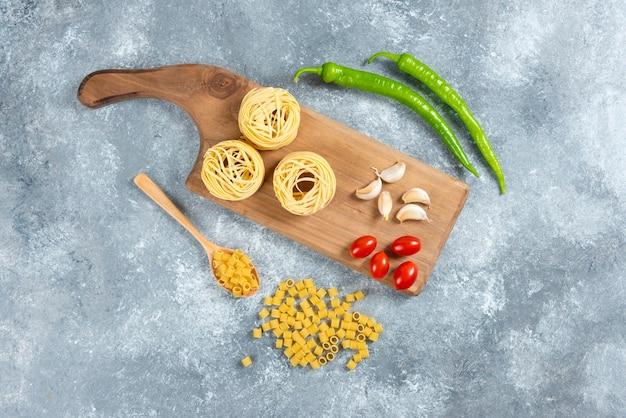 Nudeln, knoblauch und tomaten auf holzbrett.