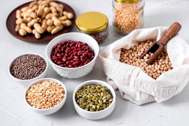 Nudeln, linsen, erdnüsse, kürbiskerne, kichererbsen und bohnen in schalen.