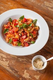 Nudeln mit basilikum und tomaten und geriebenem käse auf hölzernem hintergrund