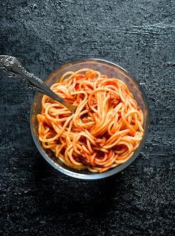 Nudeln mit bolognese-sauce in einer glasschüssel. auf schwarzem rustikalem hintergrund