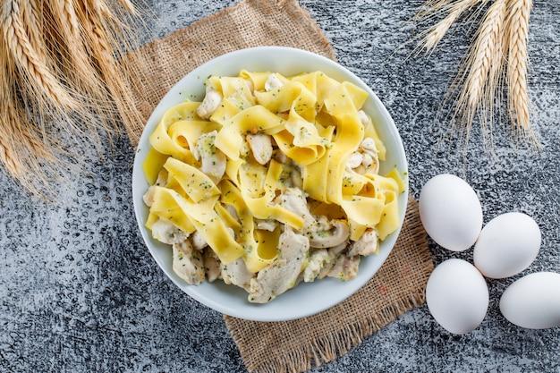 Nudeln mit fleisch in einem teller mit eiern