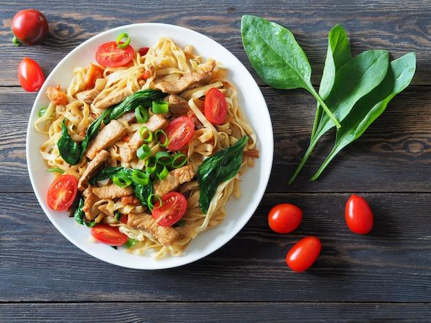 Nudeln mit frischen tomaten und spinatblättern mit gebratenen putenstücken