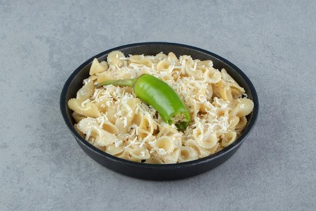 Nudeln mit geriebenem käse auf schwarzem teller.