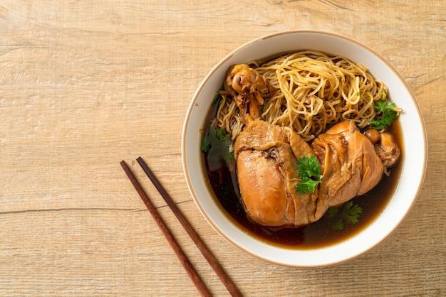 Nudeln mit geschmortem hühnchen in brauner suppenschüssel - asiatische küche