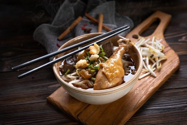 Nudeln mit hähnchenkeule und hähnchenfilet, blut mit suppe nach thailändischer art und gemüse. nudeln fürs boot. selektiver fokus