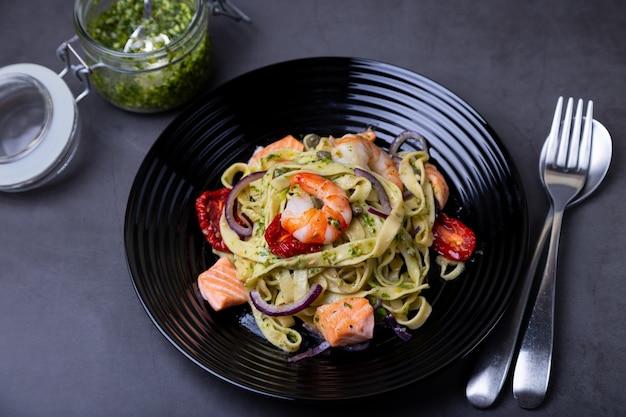 Nudeln mit meeresfrüchten, sonnengetrockneten tomaten, kapern und roten zwiebeln. hausgemachte pasta mit garnelen, lachs (forelle) und pesto-sauce. schwarzer hintergrund, schwarze platte. nahansicht.