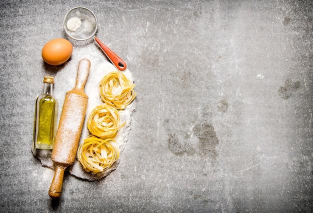 Nudeln mit olivenöl, sieb, nudelholz und mehl auf einem steinständer. auf dem steintisch. freier platz für text. draufsicht
