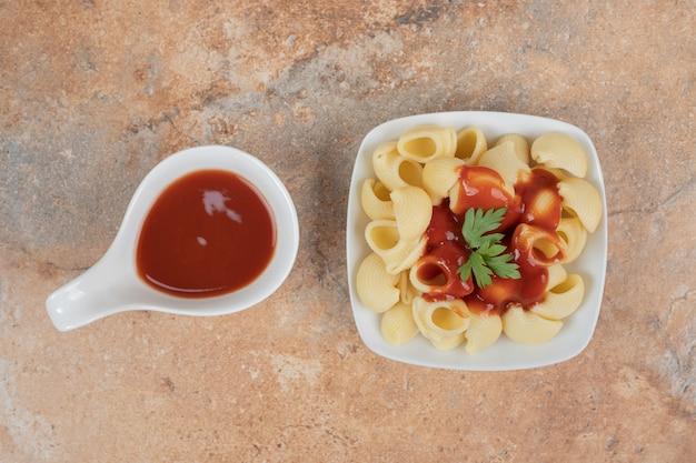 Nudeln mit petersilie und sauce auf orangefarbenem hintergrund mit ketchup