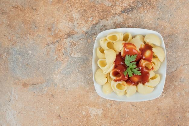 Nudeln mit petersilie und tomatensauce in weißer schüssel