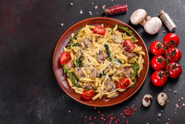 Nudeln mit pilzen, käse, spinat, rukkola und kirschtomaten. italienisches gericht, mediterrane kultur