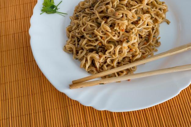 Nudeln mit rindfleisch in rechteckplatte mit bambus stic
