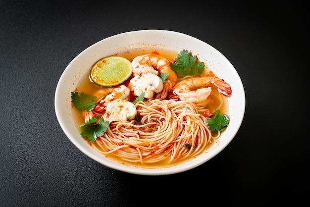 Nudeln mit scharfer suppe und garnelen in weißer schüssel (tom yum kung) - asiatische küche