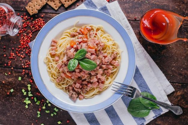 Nudeln mit schinken und tomaten auf dem tisch, restaurantgericht auf einer hölzernen hintergrundoberansicht