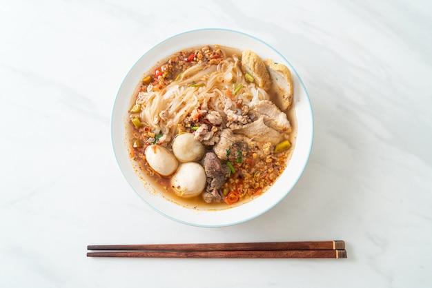 Nudeln mit schweinefleisch und frikadellen in scharfer suppe oder tom yum nudeln nach asiatischer art