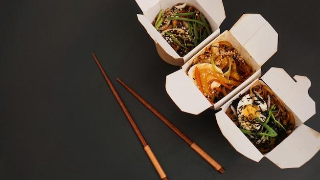 Nudeln mit schweinefleisch und gemüse in der take-out-box auf schwarzem tisch. asiatische lebensmittellieferung. lebensmittel in papierbehältern auf schwarzem tisch