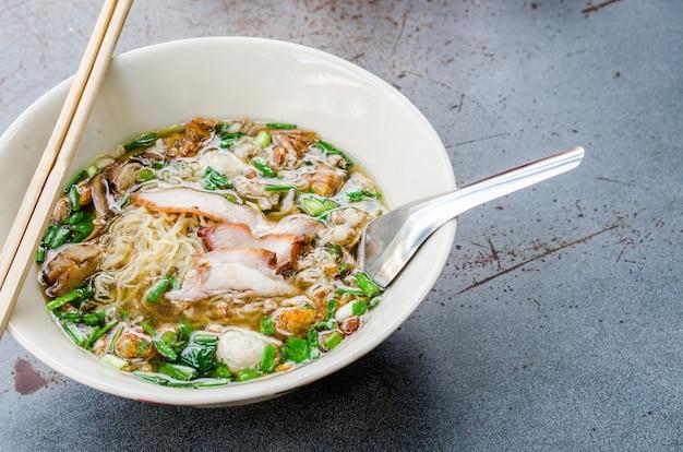 Nudeln mit schweinefleisch und schweinefleischbällchen mit suppe nach thailändischer art.