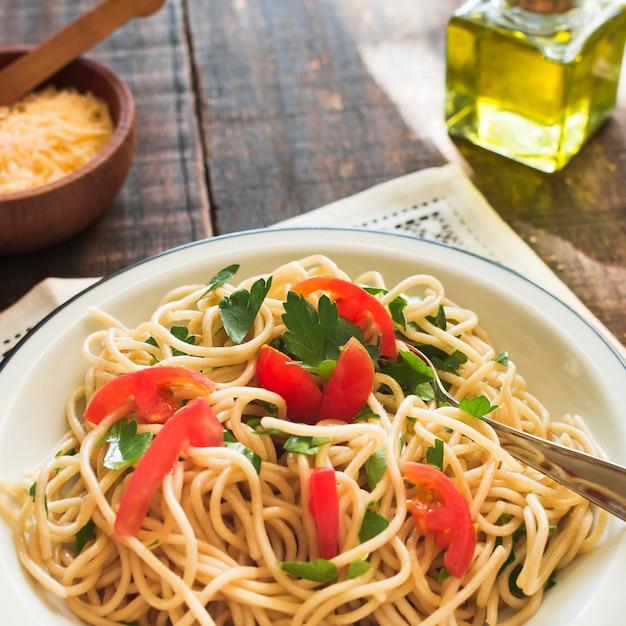 Nudeln mit tomaten und korianderblättern auf platte