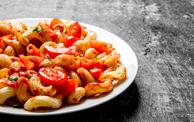 Nudeln mit tomatenscheiben auf einem teller. auf schwarzem rustikalem hintergrund