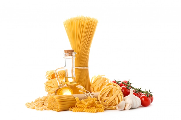 Nudeln, olivenöl, tomaten und knoblauch isoliert auf weiß. ungekochte vollkornnudeln