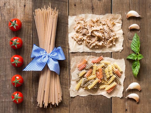 Nudeln, tomaten, knoblauch und basilikum auf hölzernem hintergrund draufsicht