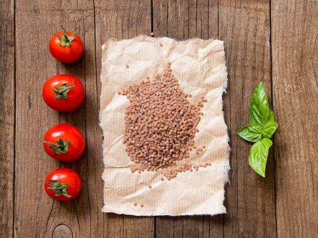 Nudeln, tomaten und basilikum auf hölzernem hintergrund draufsicht