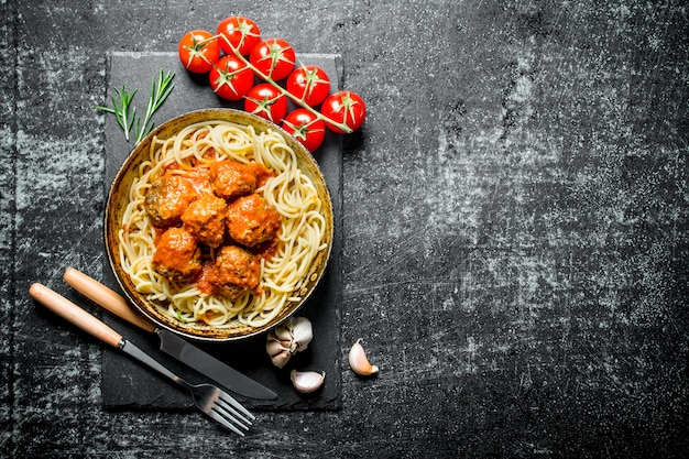 Nudeln und fleischbällchen in alter pfanne mit knoblauch und tomaten. auf schwarzem rustikalem hintergrund