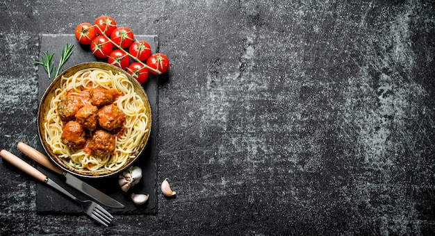 Nudeln und fleischbällchen in alter pfanne mit knoblauch und tomaten.