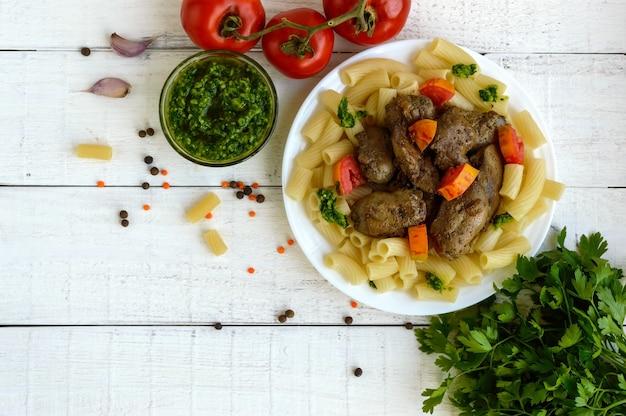 Nudeln und gebratene gänseleber (huhn, ente) mit pesto und tomate auf einer weißen oberfläche. die draufsicht