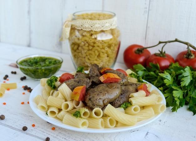 Nudeln und gebratene gänseleber (huhn, ente) mit pesto und tomate auf einer weißen oberfläche.