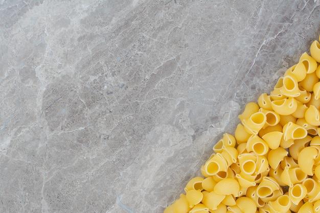 Nudeln verteilen sich auf der grauen marmoroberfläche