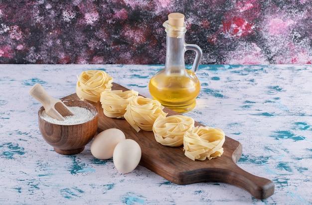 Nudelnester auf holzbrett mit mehl, eiern und olivenöl.
