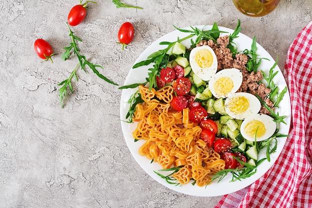 Nudelsalat mit frischem gemüse, eiern und thunfisch in einer weißen schüssel. mittagessen essen. draufsicht. flach liegen