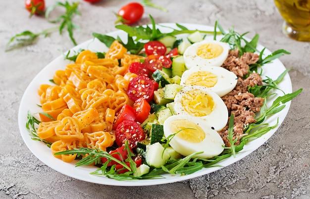 Nudelsalat mit frischem gemüse, eiern und thunfisch in einer weißen schüssel. mittagessen essen.