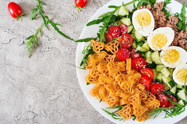 Nudelsalat mit frischgemüse, eiern und thunfisch in einer weißen schüssel. mittagessen essen. ansicht von oben. flach liegen
