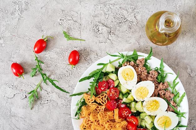 Nudelsalat mit frischgemüse, eiern und thunfisch in einer weißen schüssel. mittagessen essen.