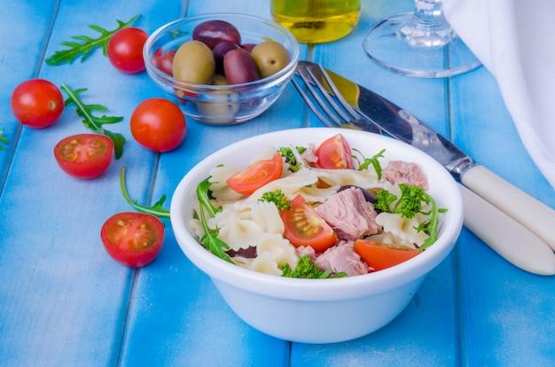 Nudelsalat mit thunfisch, oliven, kirschtomaten und rucola