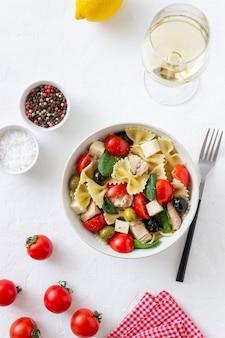 Nudelsalat mit thunfisch, tomaten und weißkäse. farfalle. gesundes essen. diät.