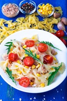 Nudelsalat mit tomaten, kirschen, thunfisch, mais und rucola,