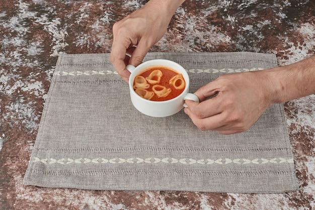 Nudelsuppe in brühe mit kräutern und gewürzen.