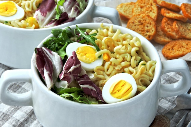 Nudelsuppe mit wachteleiern und salat mischen