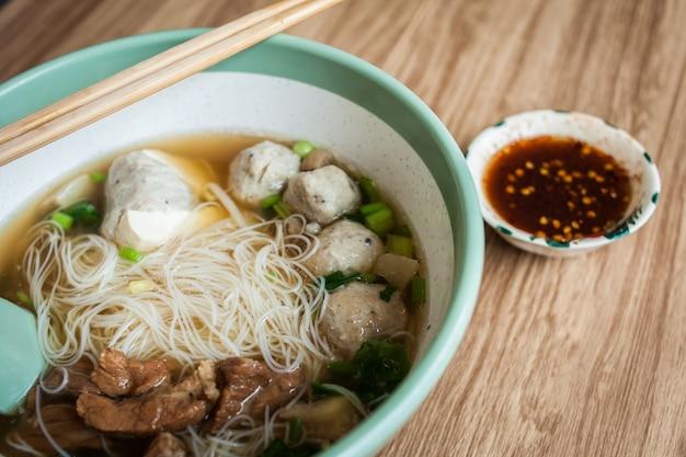 Nudelsuppe-schweinefleischfleischklöschen und tofu in der schüssel mit essstäbchen und soße