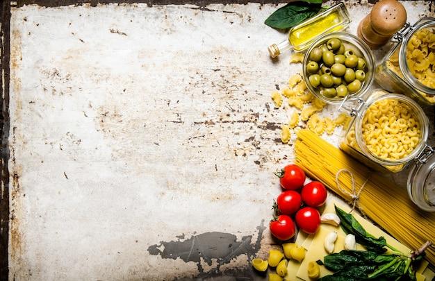 Nudeltisch. viele verschiedene nudeln, oliven, tomaten, öl und kräuter. auf rustikalem tisch. freier platz für text. draufsicht