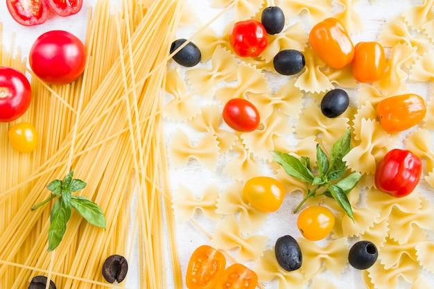Nudelzutaten, rohe nudeln, kirschtomaten, oliven und basilikumblätter auf dem weißen hintergrund