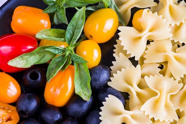 Nudelzutaten, rohe nudeln, kirschtomaten, oliven und basilikumblätter in nahaufnahme