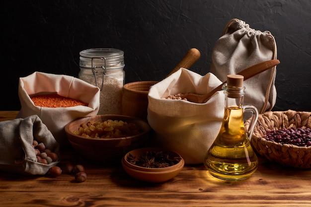 Nüsse, getrocknete früchte, macarons und grütze in öko-baumwolltaschen und gläsern auf dem holztisch in der küche