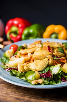 Nüsse; hühner- und sommergemüse auf einem teller über tisch