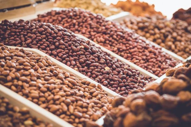 Nüsse in den regalen. verschiedene sorten von erdnüssen und mandeln.